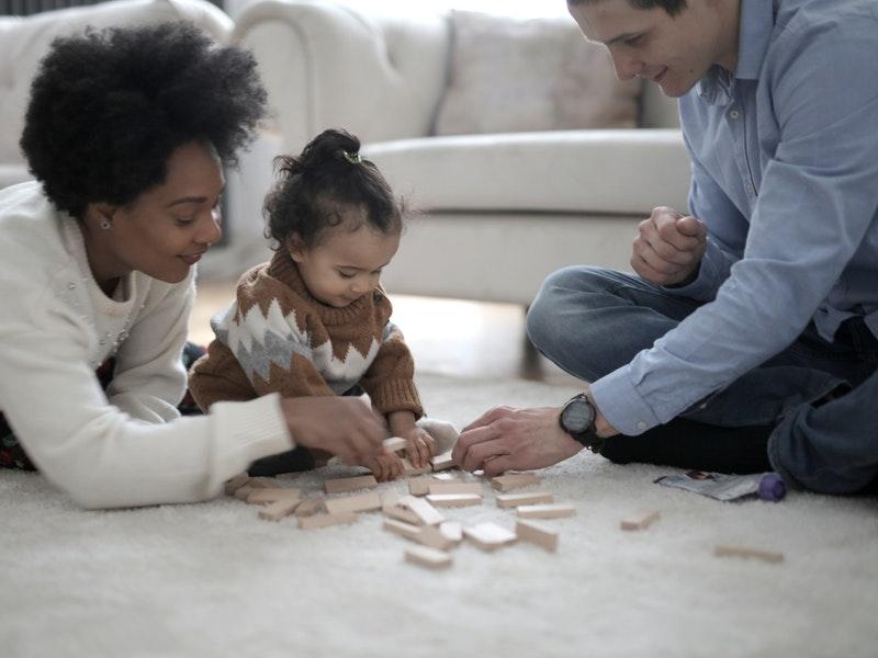 Οικογένεια που παίζει πάνω σε χαλί shaggy